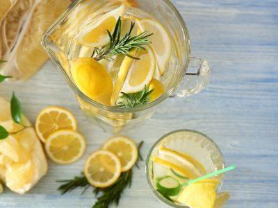 Fresh lemonade and fruits on table