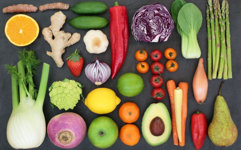 Liver detox diet health food concept with fresh fruit, vegetables, herbs and spices. Foods high in antioxidants, anthocaynins, vitamins &  dietary fibre. Top view on slate.