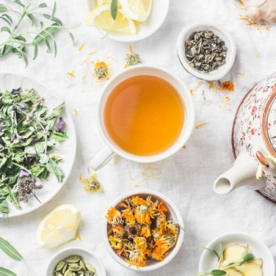 Flat lay liver detox antioxidant tea, teapot  and the ingredients for it on a light background, top view. Herbal homeopathic recept concept